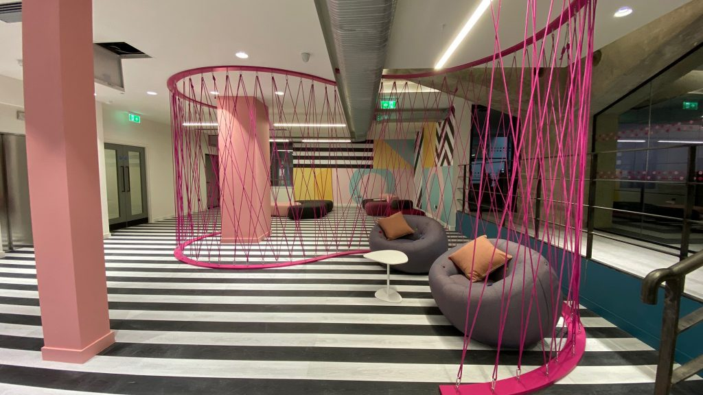 A soft seating area enclosed in pink tensioned cables.